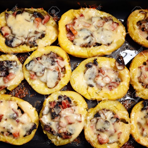 Baked potatoes with mushrooms, meat and cheese.